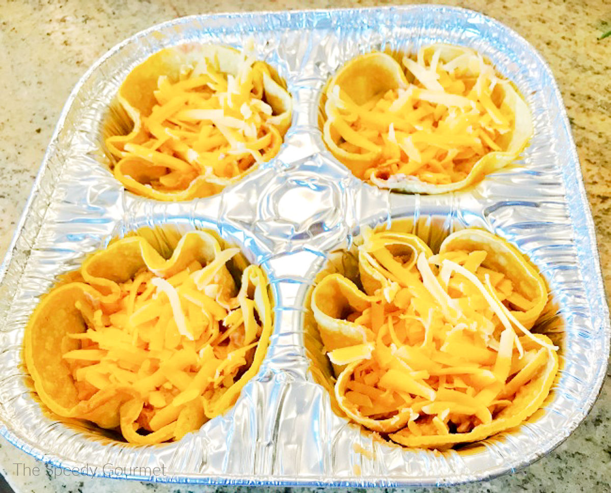 Preparing a muffin tin with tortillas and cheese